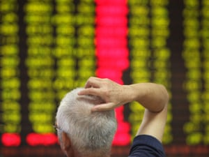 man standing in front of stocks screen