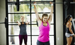 Women doing snatch with barbell in crossfit gym.