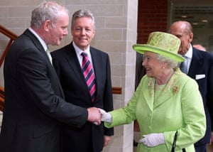 Queen Elizabeth II shakes hands with Northern Ireland Deputy First Minister Martin McGuinness watched by First Minister Peter Robinson in Belfast, Northern Ireland, 27 June 2012