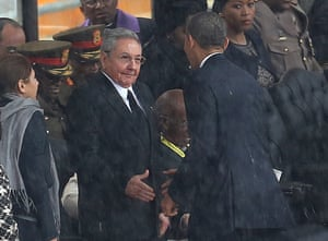 """FILE - In this Tuesday Dec. 10, 2013 file photo, U.S. President Barack Obama shakes hands with Cuban President Raul Castro, as it rains during a memorial service for former South African President Nelson Mandela, at the FNB Stadium in Soweto, South Africa. Fidel Castro says his brother Raul introduced himself to Obama in English, telling him, """"Mr. President, I'm Castro,"""" as the two leaders shook hands. The Dec. 10 handshake set off speculation in the U.S. and Cuba about whether it signaled a warming of ties between the two nations after decades of animosity. U.S. and Cuban officials dismissed that, calling the handshake a mere courtesy. (AP Photo/File) SOUTH AFRICA OUTmwshake"""