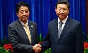 Japan's prime minister Shinzo Abe, left, and China's president Xi Jinping shake hands during their meeting on the sidelines of the Asia-Pacific Economic Cooperation (APEC) summit in Beijing on 10 November.