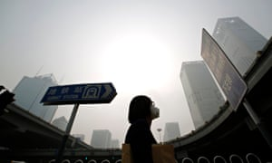 A woman wears a mask against heavy smog in Beijing