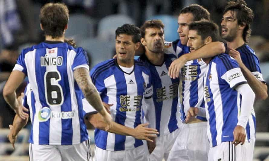 Real Sociedad striker Carlos Vela celebrates with team-mates after scoring against Atlético Madrid.