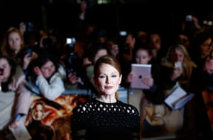 Julianne Moore, who plays Alma Coin in The Hunger Games: Mockingjay, Part 1, poses before a backdrop of adoring fans who lined the red carpet in London.