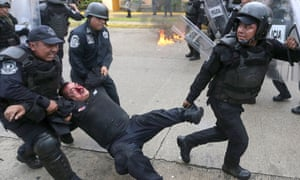 A wounded riot police officer is rescued from violent demonstrators during clashes near Acapulco's airport.