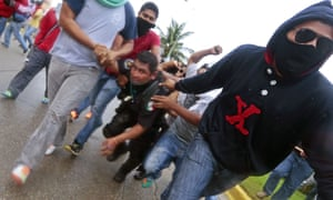 Demonstrators hold a riot police officer during clashes following a protest in Acapulco.