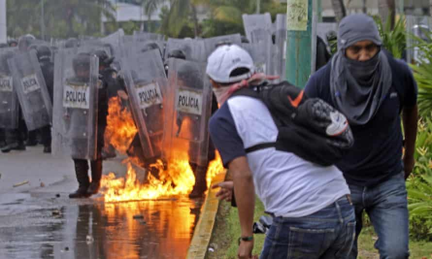 Riot police stamp out flames after a fire bomb was thrown at them during violent protests in Acapulco.