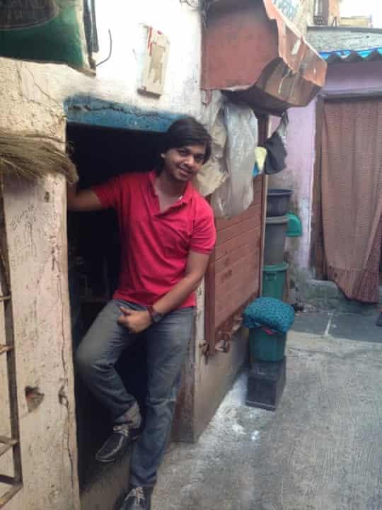 Inder Vhatwar standing in the doorway of his old house in the Golibar slum