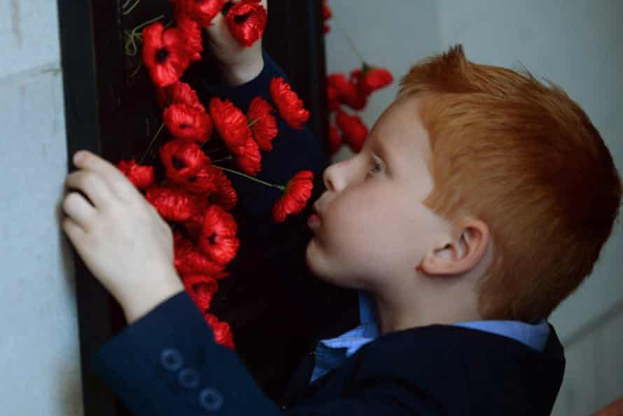 Five-year-old Alex Hopkins places a poppy next to his father's name at the Australian War Memorial in Canberra.