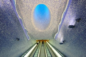 """People walk in the """"Cathedral"""" with the Crater of Luz by artist Oscar Tusquet Blanca in the Toledo subway station as part of the """"Art Station Line 1"""" project in Naples, Italy"""