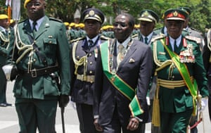 Robert Mugabe arrives at the parliament in Harare flanked by guards.