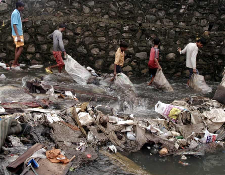 Indian slum-dwellers hunt for valuables in debris washed away by floods in Mumbai on July 30, 2005.