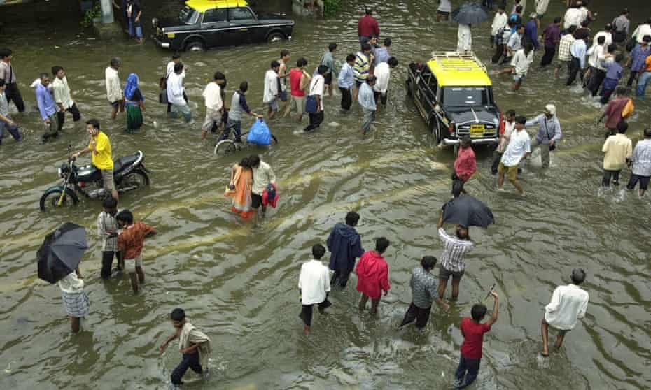 People walk through water after heavy rains in July, 2005.