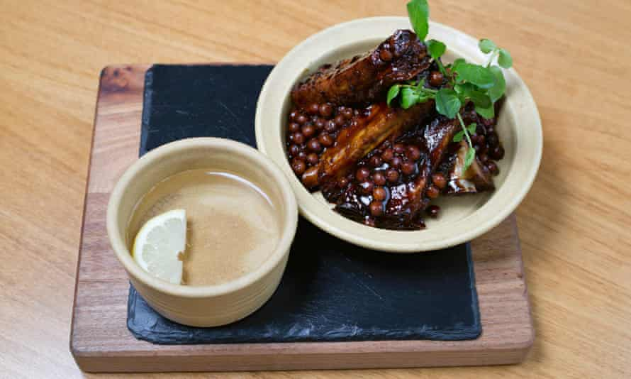Treacle-baked ribs in a high-sided dish on a wooden platter