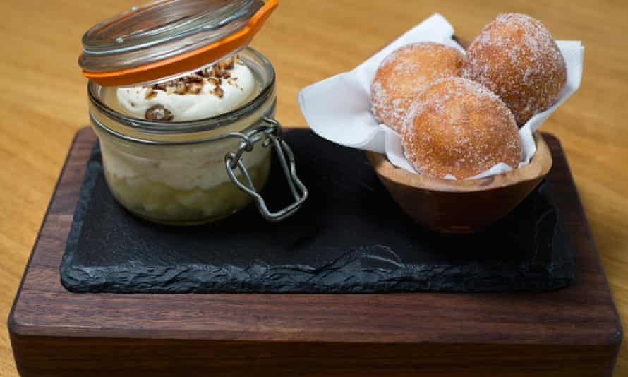 Apple trifle in a jar with on a wooden board with doughnuts in a basket