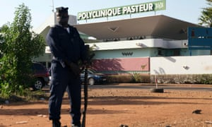 A police officer stands guard outside the quarantined Pasteur Clinic in Bamako where Mali's second case of Ebola was confirmed.
