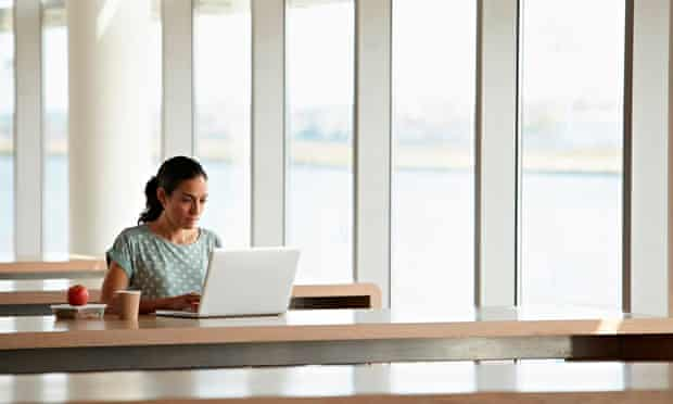 Young woman at row of desks with open laptop and apple