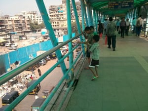 Children flying a polythene bag as a kite on a Bandra East skywalk
