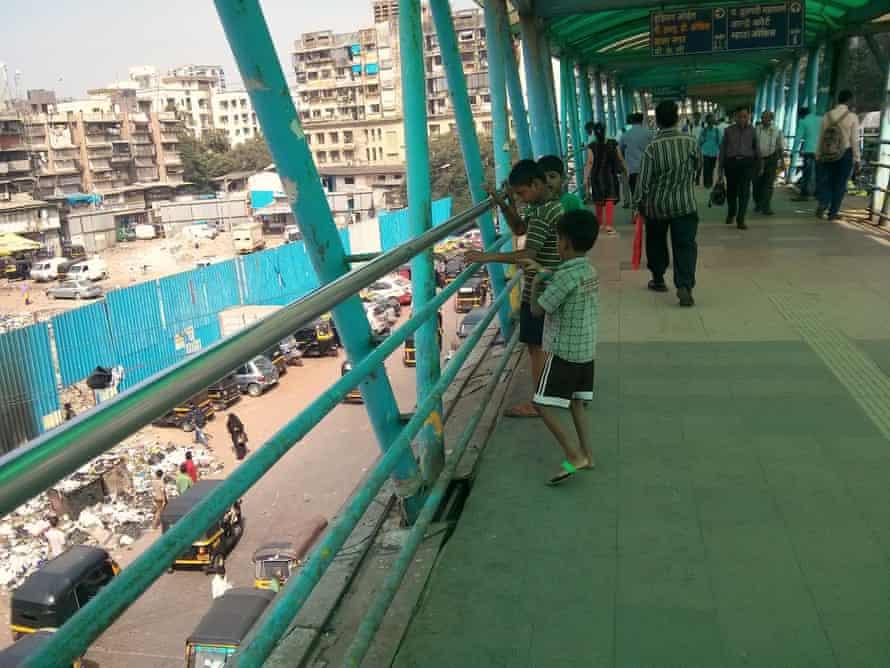 Children flying a polythene bag as a kite on a Bandra East skywalk
