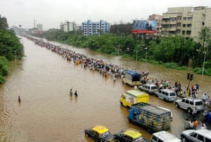 Indian commuters walk through floodwaters 27 July 2005 after torrential rains paralysed the city.