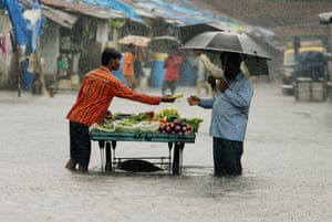 Business as usual ... a man buys vegetables on a flooded Mumbai street.