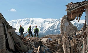 Firemen and rescuers survey the aftermath of an earthquake in L'Aquila
