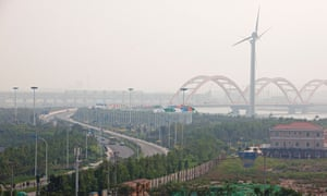 Wind turbines stand at the entrance to the Sino-Singapore Tianjin Eco-city in the Binhai New Area of Tianjin.
