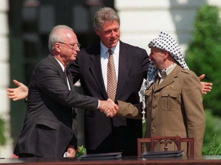 Yasser Arafat shakes hands with Israeli prime minister Yitzhak Rabin, watched by US president Bill Clinton, after the signing of the Oslo peace accord, in Washington in 1993.