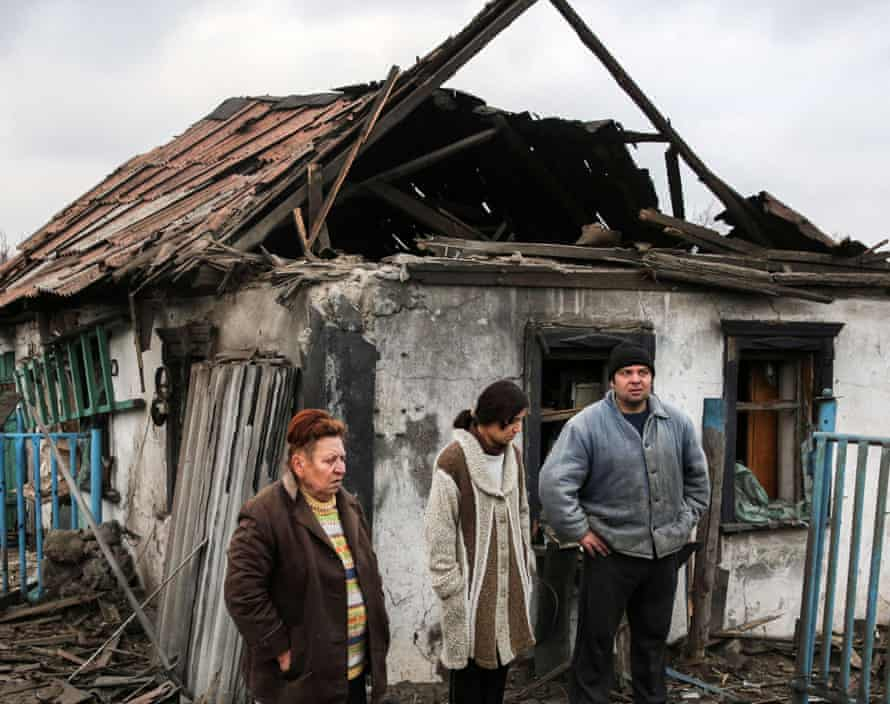 Residents outside a house destroyed during an artillery attack by the Ukrainian army in Donetsk's Petrovsky district.
