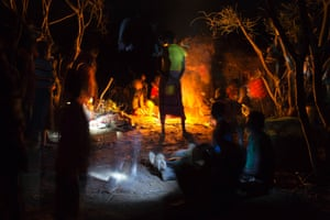 Members of the Pokot tribe gather round a fire the evening before a female circumcision ceremony, about 80 kilometres from the town of Marigat