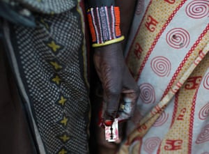 A Pokot woman holds a razor blade after performing a circumcision on four girls
