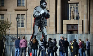 Tourists stand beneath The Shadow Boxer, a public art commission in Johannesburg.