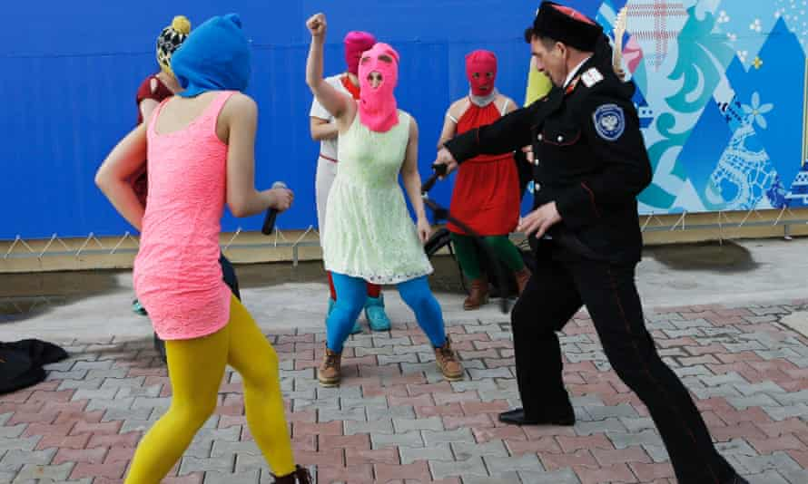 Members of the punk group Pussy Riot, including Nadezhda (Nadya) Tolokonnikova in the blue balaclava and Maria Alyokhina in the pink balaclava, are attacked by Cossack militia in Sochi, Russia, on 19 February 2014.