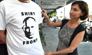 """Fiona Stager inspects a t-shirt her shop will give away featuring Russia's President Valdimir Putin and a quote from Australia's Prime Minister Tony Abbott threatening to """"shirt front"""" Putin"""