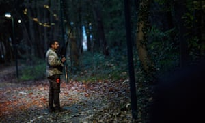 A member of the police animal brigade walks through a wood in Montevrain