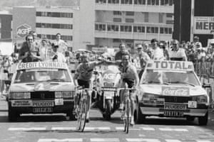 Bernard Hinault, right, and his teammate Greg Lemond smile as they cross the finish line together at the end of the 18th stage of the 1986 Tour de France