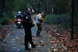 Members of the police animal brigade walk through a wood in Montevrain, east of Paris. French authorities say a young tiger is on the loose near Disneyland Paris, one of Europe's top tourist destinations, and have urged residents in three towns to stay indoors. (