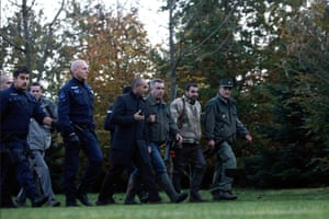 Members of the police animal brigade walk through a wood close to Montevrain, east of Paris. French authorities say a young tiger is on the loose near Disneyland Paris, one of Europe's top tourist destinations, and have urged residents in three towns to stay indoors.