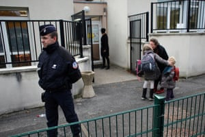 Police officers stand next to a school in Montevrain, east of Paris.  Scores of police patrolled a small town west of the French capital on Thursday night after a tiger eluded a massive search and remained on the prowl in the region near Disneyland Paris. (
