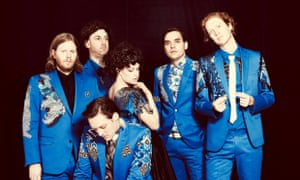 Arcade Fire band group shot against a black background, all wearing bright blue suits with applique patchwork.