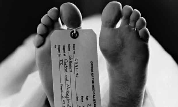 The feet of a body in a morgue with a tag around the toe