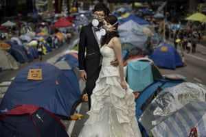 Kevin Frayer, a regular contributor to the 20 photographs, was covering the pro-democracy protests in Hong Kong. Here, a young couple wear gas masks as they pose for a wedding photographer prior to their marriage.