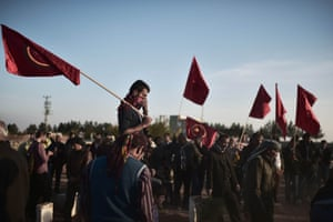 """Photographer Aris Messinis continued his strong reportage from the Turkish-Syrian border town of Suruç. In this photograph, Kurdish people attend the funeral of a """"People's Protection Unit"""" fighter who died in Kobane, also known as Ain al-Arab. The Syrian Observatory for Human Rights reported that Kurdish forces fighting Islamic State had cut off a key supply route used by the jihadists. <a href=""""http://www.theguardian.com/artanddesign/gallery/2014/nov/14/fighting-in-kobani-syria-in-pictures"""">Click here to view more of Messinis' work from Suruç</a>"""