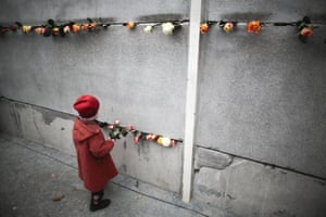 Three-year-old Hulda pushes flowers into cracks at a remaining section of the Berlin Wall at Bernauer Strasse, to commemorate its victims. Sunday, 9 November was the 25th anniversary of the fall of the Wall, when the East German government lifted travel restrictions and thousands of East Berliners pushed their way past perplexed border guards to join with their brethren in the West.