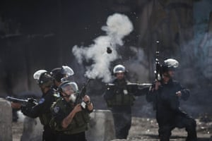 In Ramallah, an Israeli border policeman fires a teargas canister at Palestinian protesters following a demonstration against Israeli restrictions on Muslims wishing to perform Friday prayers at Al-Aqsa Mosque in Jerusalem.