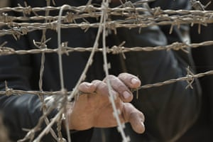 A Syrian Kurd holds his hand on the barbed wire fence that marks the Turkish-Syrian border, on the outskirts of Kobane