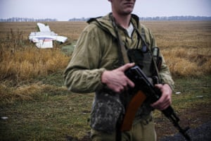 A pro-Russian gunman stands guard next to parts of the Malaysia Airlines Flight MH17 at the crash site near the village of Hrabove.