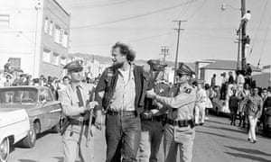 16 October 1965: Blood drips from the wrist of Michael H Walter, an Oakland member of the Hell's Angels motorcycle club, as he is taken into custody by Berkeley police officers after breaking through police lines, tearing down a placard and battling some of the Vietnam protest marchers in Berkeley. A police officer was seriously injured in the melee and Walters was jailed