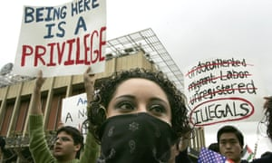 10 April 2006: An opponent of House bill HR4437 wears a mask as she stands in front of placards supporting the bill at a rally for immigration rights at University of California, Berkeley. Thousands protested against HR4437 across the US on what was called the National Day of Action on Immigrant Rights