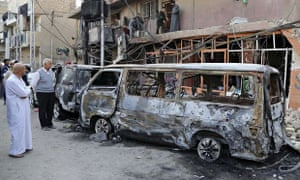 Iraqis inspect the site of a car bomb in Baghdad